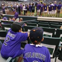 Photo - Young fans wear misspelled jerseys given to fans with the name of Colorado Rockies All-Star shortstop Troy Tulowitzki before a Rockies against the Pittsburgh Pirates baseball game in Denver, Saturday, July 26, 2014. (AP Photo/David Zalubowski)