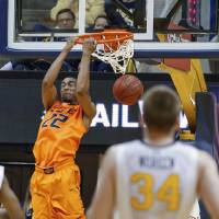 Photo - Oklahoma State's Markel Brown (22) dunks during the second half of an NCAA college basketball game in Morgantown, W.Va., on Saturday, Feb. 23, 2013. Oklahoma State defeated West Virginia 73-57. (AP Photo/David Smith) ORG XMIT: WVDS108