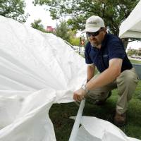 Photo - jason Klontz, Edmond, sets up a canopy after claiming his tailgater spot (fifth year in the same spot) across from Gaylord Family-Oklahoma Memorial Stadium in Norman, Okla. on Friday, Aug. 29, 2014. Photo by Steve Sisney, The Oklahoman