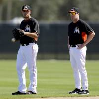 Photo - Miami Marlins pitcher Jose Fernandez, left, and manager Mike Redmond talk during spring training baseball practice Sunday, Feb. 16, 2014, in Jupiter, Fla. (AP Photo/Jeff Roberson)