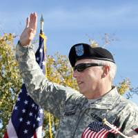 Photo - Maj. Gen. Myles Deering, the state's adjutant general, waves to the crowd at last year's Veterans Day parade in Norman.