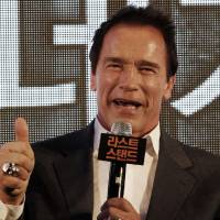 Photo - Actor Arnold Schwarzenegger gestures during a press conference to promote his latest film
