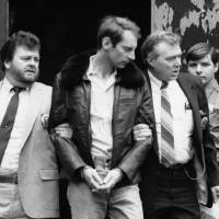 Photo - FILE - In this Wednesday, Jan. 16, 1985 file photo, Bernhard Goetz, second from left, is escorted by police as he is taken out of criminal court in New York. Police say Goetz, 65, was nabbed in a sting operation in Union Square on Friday afternoon, Nov. 1, 2013 selling $30 worth of marijuana to an undercover officer. The