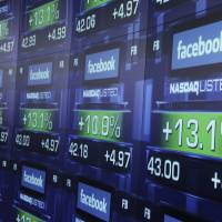 Photo -   FILE - In this Friday, May 18, 2012 file photo, electronic screens show the price of Facebook shares after they began trading in New York. A flood of analyst reports from the banks that led Facebook's initial public offering gave the company's stock a mix of