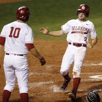 Photo - OU's Craig Aikin (3) celebrates with Niko Buentello (10) after the pair scored in the fourth inning during a Bedlam college baseball game between Oklahoma and Oklahoma State in the Big 12 baseball tournament at the Chickasaw Bricktown Ballpark in Oklahoma City,  Friday, May 23, 2014. Photo by Nate Billings, The Oklahoman