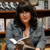 Photo - Author E L James holds a copy of her erotic fiction book