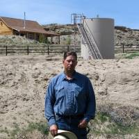 Photo -   ADVANCE FOR FRIDAY AMS MAY 4 - FILE - A May 22, 2009 picture shows John Fenton, a farmer who lives near Pavillion in central Wyoming, near a tank used in natural gas extraction, in background. Fenton and some of his neighbors blame hydraulic fracturing, or
