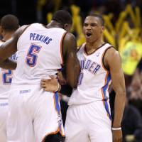 Photo - Oklahoma City Thunder guard Russell Westbrook, right, celebrates with teammate Kendrick Perkins, left, after a basket in the fourth quarter of an NBA basketball game against the Portland Trail Blazers, in Oklahoma City, Sunday, March 27, 2011. Oklahoma City won 99-90. (AP Photo/Sue Ogrocki) ORG XMIT: OKSO107