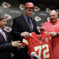 Photo - Kansas City Chiefs No. 1 draft pick Eric Fisher, an offensive lineman from Central Michigan, poses with coach Andy Reid, right, and owner Clark Hunt, left, during an NFL football news conference Friday, April 26, 2013, in Kansas City, Mo. Fisher was the No. 1 overall pick in the NFL draft on Thursday. (AP Photo/Charlie Riedel)