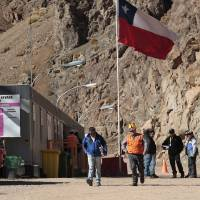 Photo - In this May 23, 2013 photo, security officers walk away from the entrance of the Barrick Gold Corp's Pascua-Lama facilities, in northern Chile. Chile's environmental regulator blocked Barrick Gold Corp.'s $8.5 billion Pascua-Lama project on Friday, May 24, 2013, and imposed its maximum fine on the world's largest gold miner, citing