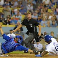 Photo - Los Angeles Dodgers' Yasiel Puig, right, scores on a fielders' choice by Hanley Ramirez as Chicago Cubs catcher Welington Castillo, left, reaches to tag him as home plate umpire Jim Wolf looks on during the sixth inning of a baseball game, Friday, Aug. 1, 2014, in Los Angeles. (AP Photo/Mark J. Terrill)