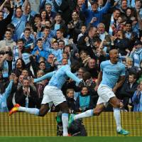Photo - Manchester City's Vincent Kompany, right, celebrates after scoring against West Ham during the English Premier League soccer match between Manchester City and West Ham United at the Etihad Stadium, Manchester, England, Sunday, May 11, 2014. (AP Photo/Rui Vieira)