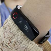 Photo - In this June 5, 2014 photo, a reporter shows LG's Lifeband Touch for photographs in Seoul, South Korea. LG Electronics Inc. has entered the fledging market for wearable gadgets with a wristband that tracks workouts and calories burned. (AP Photo/Lee Jin-man)