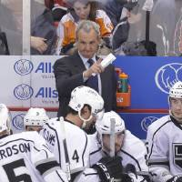 Photo - Los Angeles Kings head coach Darryl Sutter talks to his team during a timeout in the second period of an NHL hockey game against the Detroit Red Wings in Detroit, Wednesday, April 24, 2013. (AP Photo/Carlos Osorio)