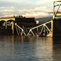 Photo - People look on after the Interstate 5 bridge collapsed over the Skagit River in Mount Vernon, Wash., Thursday, May 23, 2013. (AP Photo/The Seattle Times, Rick Lund)  TV OUT; USA TODAY OUT; MAGS OUT; NO SALES; SEATTLEPI.COM OUT; MANDATORY CREDIT