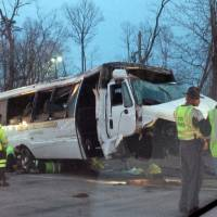 Photo - This photo provided by the Virginia State Police,  police investigate the scene of a bus accident on Interstate 95, early Sunday, March 23, 2014 in Fairfax County, Va.  The shuttle bus struck a guardrail and overturned before dawn Sunday just south of the nation's capital, leaving at least one person dead and sending 16 others to the hospital, Virginia State Police said.  The bus was headed south on the heavily traveled East Coast artery when witnesses reported a white, speeding four-door passenger vehicle swerved into the bus's travel lane. The bus then swerved to the right to avoid the sedan, ran off the road, struck the guardrail and overturned, Virginia State Police said. The crash occurred on the interstate in northern Virginia's Fairfax County and police were called at 3:28 a.m. Sunday, State Police spokeswoman Corinne Geller said. (AP Photo/Virginia State Police)