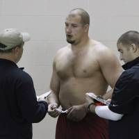 Photo -  Offensive lineman Lane Johnson talks with NFL scouts during Oklahoma's NFL football pro day in Norman, Okla., Wednesday, March 13, 2013. (AP Photo/Alonzo Adams) ORG XMIT: OKAA103