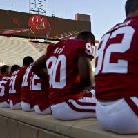 Photo - OU COLLEGE FOOTBALL: The new scoreboard looms in the background as Oklahoma football players sit along the wall waiting for photo and interviews  during the University of Oklahoma (OU) media day at the Gaylord Family -- Oklahoma Memorial Stadium on Wednesday, Aug. 6, 2008, in Norman, Okla.   Staff Photo By CHRIS LANDSBERGER ORG XMIT: KOD