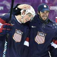 Photo - United States forward T.J. Oshie, left, is congratulated by goalie Ryan Miller, right, after Oshie scored the game-winning goal in a shootout against Russia in a men's ice hockey game at the 2014 Winter Olympics, Saturday, Feb. 15, 2014, in Sochi, Russia. The U.S. won 3-2 in a shootout. (AP Photo/The Canadian Press, Nathan Denette)