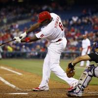Photo - Philadelphia Phillies' Ryan Howard follows through after hitting an RBI single off Colorado Rockies starting pitcher Jordan Lyles during the third inning of a baseball game, Wednesday, May 28, 2014, in Philadelphia. At right is catcher Wilin Rosario. (AP Photo/Matt Slocum)