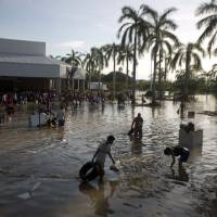 Photo - People wade through waist-high water in a store's parking, looking for valuables, south of Acapulco, in Punta Diamante, Mexico, Wednesday, Sept. 18, 2013. Mexico was hit by the one-two punch of twin storms over the weekend, and the storm that soaked Acapulco on Sunday - Manuel -re-formed into a tropical storm Wednesday, threatening to bring more flooding to the country's northern coast. With roads blocked by landslides, rockslides, floods and collapsed bridges, Acapulco was cut off from road transport. (AP Photo/Eduardo Verdugo)