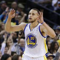 Photo - Golden State Warriors' Stephen Curry celebrates after scoring against the Utah Jazz during the first half of an NBA basketball game, Sunday, April 7, 2013, in Oakland, Calif. (AP Photo/Ben Margot)
