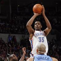 Photo - Oklahoma City's Kevin Durant (35) takes a shot over Carlos Boozer (5) of Utah in the second half during the NBA basketball game between the Oklahoma City Thunder and the Utah Jazz at the Ford Center in Oklahoma City, Thursday, December 31, 2009. The Thunder won, 87-86. Photo by Nate Billings, The Oklahoman ORG XMIT: KOD