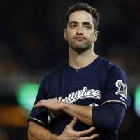 Photo - FILE - In this Sept. 21, 2012, file photo, Milwaukee Brewers Ryan Braun reacts while holding his elbow after missing his swing during a baseball game against the Washington Nationals at Nationals Park in Washington. Braun says he used the person who ran the Florida clinic now under investigation by Major League Baseball as a consultant on his drug suspension appeal last year and nothing more.  Yahoo Sports reported Tuesday, Feb. 5, 2012, that his name showed up three times in records of the Biogenesis of America LLC clinic.  (AP Photo/Jacquelyn Martin, FIle)