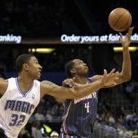 Photo -   Orlando Magic's Justin Harper (32) and Charlotte Bobcats' Derrick Brown (4) go after the loose ball during the first half of an NBA basketball game, Wednesday, April 25, 2012, in Orlando, Fla. (AP Photo/John Raoux)