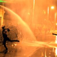 Photo - Egyptian protesters throw stones while security police open water cannons on them from inside the grounds of the presidential palace during a demonstration in Cairo, Egypt, Monday, Feb. 11, 2013. Security forces sprayed protesters with water hoses and tear gas outside the presidential palace Monday as Egyptians marked the second anniversary of autocrat Hosni Mubarak's ouster with angry demonstrations against his elected successor.(AP Photo/Khalil Hamra)