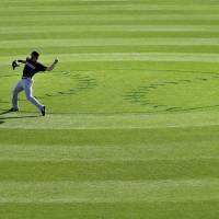 Photo - Colorado Rockies left fielder Charlie Blackmon warms up before starting the bottom of the ninth inning against the Kansas City Royals in a spring training baseball game Tuesday, March 19, 2013, in Surprise, Ariz. (AP Photo/Gregory Bull)