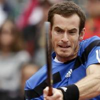 Photo - Britain's Andy Murray slams a backhand shot in his 6-1, 6-2, 6-3 victory over Donald Young in a Davis Cup tennis match on Friday, Jan. 31, 2014, in San Diego. (AP Photo/Lenny Ignelzi)