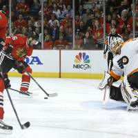 Photo - Chicago Blackhawks center Michal Handzus (26) scores past Philadelphia Flyers goalie Ray Emery, right, off a pass from Marcus Kruger, left, during the second period of an NHL hockey game on Wednesday, Dec. 11, 2013, in Chicago. (AP Photo/Charles Rex Arbogast)