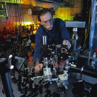 Photo -   In this 2003 photo provided by Geoffrey Wheeler and the National Institute of Standards and Technology, physicist David Wineland adjusts an ultraviolet laser beam used to manipulate ions in a high-vacuum apparatus containing an