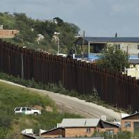 Photo -   In this photo taken Thursday, Aug. 9, 2012, A U.S. Border Patrol vehicle keeps watch along the border fence in Nogales, Ariz. A U.S. Border Patrol agent opened fire on a group of people throwing rocks from across the Mexican border, killing a teenage boy and eliciting outrage from the Mexican government over the use of lethal force, authorities said Thursday.(AP Photo/Ross D. Franklin)
