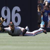 Photo - San Francisco Giants center fielder Gregor Blanco makes a diving catch on a line drive by San Diego Padres' Will Venable during the first  inning of a baseball game Saturday, July 5, 2014, in San Diego. (AP Photo/Don Boomer)