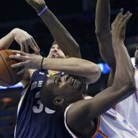 Photo -   Memphis Grizzlies center Marc Gasol, left, wraps up Oklahoma City Thunder forward Kevin Durant, center, as he grabs a rebound in the second quarter of an NBA basketball game in Oklahoma City, Wednesday, Nov. 14, 2012. Oklahoma City Thunder forward Serge Ibaka (9) is at right. (AP Photo/Sue Ogrocki)