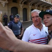Photo - France head coach Didier Deschamps poses for a selfie with a fan before the start of Deschamps' press conference at the Teatro Pedro II, in Ribeirao Preto, Brazil, Friday, July 1, 2014. France will face Germany in their World Cup quarterfinal, Friday. (AP Photo/David Vincent)