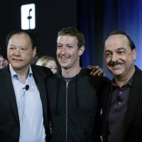 Photo - From left, HTC CEO Peter Chou, Facebook CEO Mark Zuckerberg and AT&T Mobility CEO Ralph De La Vega embrace as they show joint products at Facebook headquarters in Menlo Park, Calif., Thursday, April 4, 2013. (AP Photo/Marcio Jose Sanchez)