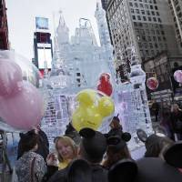Photo -   People with mouse ear caps and balloons gather near a three-story castle mad of ice in New York's Times Square, Wednesday, Oct. 17, 2012. On Wednesday, Disney announced a new program for 2013,