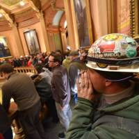 Photo - Brett Brown or Owosso, Mich., chants as Pro-union demonstrators crowd the Rotunda in Lansing, Mich.,  to chant Wednesday afternoon Dec. 5, 2012, in the Capitol after House and Senate Democrats said there was a possibility of