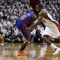 Photo -   New York Knicks' Iman Shumpert (21) pulls on his leg after injuring it in the second half during an NBA basketball game in the first round of the Eastern Conference playoffs in Miami, Saturday, April 28, 2012. At right is Miami Heat's Mario Chalmers. (AP Photo/Lynne Sladky)