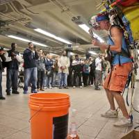 Photo - In this Wednesday, Oct. 9, 2013, photo, subway riders pause to listen as Jeffrey Masin, right, performs his one-man band ensemble at a subway platform at Union Square station in New York. Masin, from Waterford, Conn., has performed his one-man band show he calls