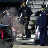 Photo -   President Barack Obama salutes as he deplanes Air Force One on his early-morning arrival in Madison, Wis., Monday, Nov. 5, 2012. (AP Photo/Andy Manis)
