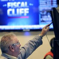 Photo -   FILE - In this Nov. 7, 2012, file photo, James Dresch of MND Partners Inc. works on the floor of the New York Stock Exchange in New York. Stocks declined for a third day on Wall Street Wednesday, Nov. 28, 2012, as investors waited for signs of progress on the