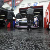 Photo - Pit crew members push the car of driver Juan Pablo Montoya into the Grand National Garage at Talladega Superspeedway in Talladega, Ala., Saturday, May 4, 2013. Rain threatens Saturday's qualifying for Sunday's NASCAR Sprint Cup seires Aaron's 499 auto race. (AP Photo/Rainier Ehrhardt)