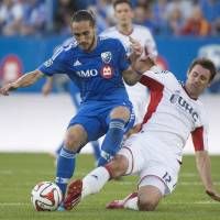 Photo - Montreal Impact's Issey Nakajima-Farran, left, battles for the ball against New England Revolution's Andy Dorman during first half MLS soccer action in Montreal, Saturday, May 31, 2014. (AP Photo/The Canadian Press, Graham Hughes)