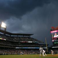 Photo - A dark cloud is seen over Citizens Bank Park as Philadelphia Phillies starting pitcher Roberto Hernandez throws before play was suspended due to rain during the fourth inning of a baseball game against the Los Angeles Dodgers, Friday, May 23, 2014, in Philadelphia. (AP Photo/Matt Slocum)