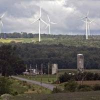 Photo - FILE--In this Aug. 4, 2008 file photo, wind turbines from the Maple Ridge Wind Farm tower over farms in Martinsburg, N.Y. A new study says New York could be completely powered by wind, water and sunlight by 2030 with a concerted push, though the state's own decade-long effort to significantly boost green energy shows how difficult that would be in practice. (AP Photo/Mike Groll, File)