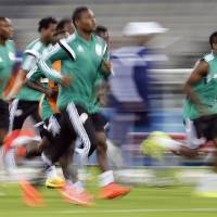 Photo - Nigerian players warm up during an official training session the day before the group F World Cup soccer match between Iran and Nigeria at the Arena da Baixada in Curitiba, Brazil, Sunday, June 15, 2014.  (AP Photo/Frank Augstein)